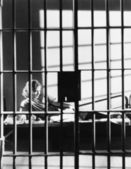 Woman through bars of jail cell — Stockfoto