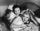 Two women in bed with telephone — Stok fotoğraf