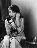 Distressed woman using telephone — Stockfoto