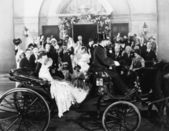 Newlyweds leaving wedding in carriage — Stock Photo