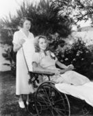 Woman in wheelchair with nurse — Stock Photo