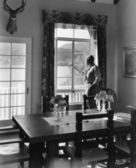 Man standing at window in dining room — Stock Photo