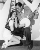 Man playing banjo for adoring woman — Stock Photo