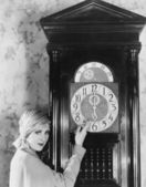 Woman with grandfather clock at midnight — Stock Photo