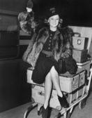 Mávající ženu sedící na hromadu zavazadel — Stock fotografie