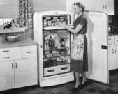 Donna con frigorifero aperto — Foto Stock