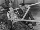 Wooden frame broken over two mens heads — ストック写真