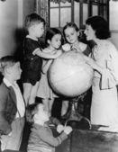 Vrouw en kinderen kijken naar globe — Stockfoto
