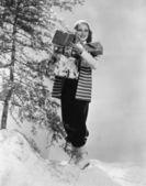 Kvinna utanför i snön med julklappar — Stockfoto