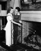 Couple roasting marshmallows over fireplace — Stock Photo