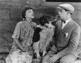 Perro en medio de las parejas beso — Foto de Stock