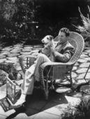 Mann, sitzend auf stuhl außerhalb mit hund — Stockfoto