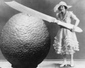 Woman with huge knife and piece of fruit — Stockfoto
