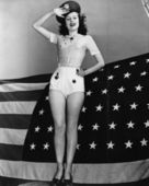 Portrait of woman saluting with American flag — Stockfoto