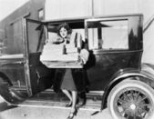 Woman carrying packages from car — Stockfoto
