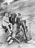 Monkey with golf clubs and toddler girl — Stock Photo