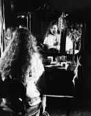 Woman at dressing table looking in mirror — Stock Photo