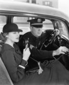 Woman using radio in car with policeman — Stock Photo