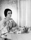 женщина, имеющая еды на таблице — Стоковое фото