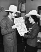 Couple with cowboy hats looking at sheet music — Stock Photo