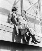 足場に一緒に座っている 2 人の女性 — ストック写真
