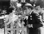 Man and woman talking over a picket fence — Stock Photo