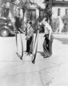 Boy and girl playing hoop and stick on a sidewalk — Stock Photo