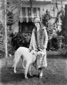 Junge frau im mantel und hut stehen außerhalb mit ihren russischen wolfhound — Stockfoto