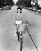 Young woman riding her bicycle with basket full of flowers and carrots — Stok fotoğraf