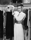 Young woman hanging up a skirt in the closet — ストック写真