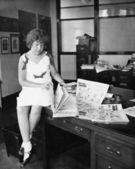 Meisje, zittend op een bureau en een krant lezen — Stockfoto
