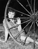 Young woman smiling while sitting behind a wagon wheel — Stock Photo