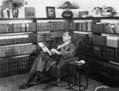 Man sitting in his library reading a book — Stock Photo