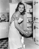 Young woman in an apron in her kitchen taking food out of the refrigerator — Stock Photo