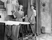 Man and woman standing in a kitchen while she is ironing his pants and he is behind a curtain — Stock Photo