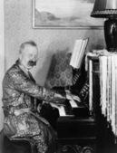 Mann in ein gewand, sein klavierspiel im wohnzimmer — Stockfoto