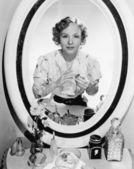 Mujer sentada frente a su vanidad mirarse en el espejo — Foto de Stock