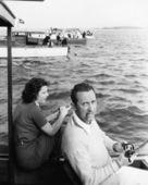 Uomo e donna seduta su una barca su un lago con la canna da pesca — Foto Stock