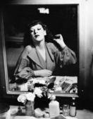 Femme assise en face de sa vanité en regardant dans le miroir — Photo