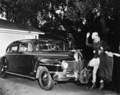Mujer frente a un coche con una bolsa de regalos de navidad — Foto de Stock