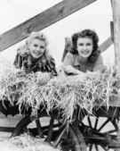 δύο γυναίκες που βρίσκεται σε ένα βαγόνι εμπορευμάτων σανού με τα πόδια τους στον αέρα — 图库照片