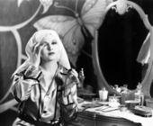 Donna seduta davanti alla sua vanità e prendendo il suo compongono — Foto Stock