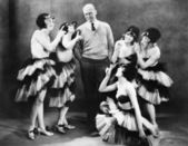 Five young women dancing around a man — Stock Photo