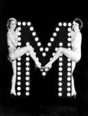 Two young women posing with the letter M — Stock Photo