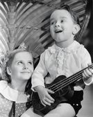 Close-up of a boy playing a guitar with his sister — Stock Photo