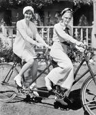Portrait of two young women sitting on a tandem bicycle — Stock Photo