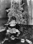 Mujer joven sentada en un sofá con un árbol de navidad en el fondo — Foto de Stock