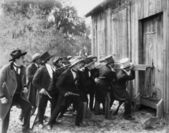 Group of men with guns and top hats breaking into a barn — Stock Photo
