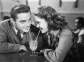 Par i en restaurang tittar på varandra och dela en mjölk shake med två sugrör — Stockfoto