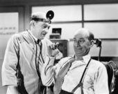 Médecin de sexe masculin à l'écoute à un homme qui est expliquer quelque chose avec ses doigts — Photo